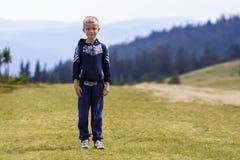 Weinig jongen met een rugzak die in toneel de zomer groene Karpatische bergen wandelen Kind bevindende alleen het genieten van la Stock Foto's