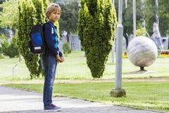 Weinig jongen met een rugzak gaat naar school De achtergrond van het stadspark Stock Afbeelding