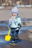 Weinig jongen met een stuk speelgoed gele schop Royalty-vrije Stock Foto's