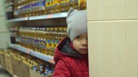 Weinig jongen met een vuil gezicht in de supermarkt stock video