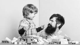 Weinig jongen met gebaarde mensenpapa die samen spelen Gelukkige Familie De zomer dreems de bouwhuis met kleurrijke aannemer royalty-vrije stock foto's