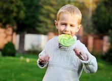 Weinig jongen met grote lolly op een stok stock afbeeldingen