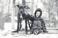 Weinig jongen met grote zwarte hond Stock Afbeeldingen