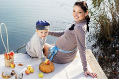 Weinig jongen met haar moeder op het de herfstmeer Stock Fotografie