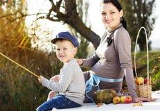 Weinig jongen met haar moeder op het de herfstmeer Stock Afbeelding