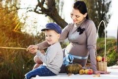 Weinig jongen met haar moeder op het de herfstmeer Stock Foto