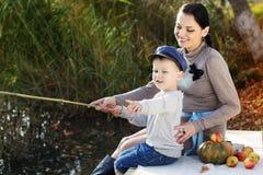 Weinig jongen met haar moeder op het de herfstmeer Royalty-vrije Stock Foto's