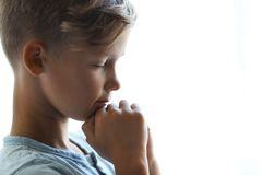 Weinig jongen met handen clasped samen voor gebed op lichte achtergrond royalty-vrije stock afbeelding