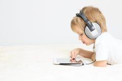 Weinig jongen met hoofdtelefoon die aanrakingsstootkussen gebruiken royalty-vrije stock foto