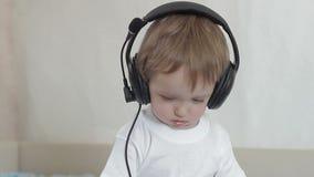 Weinig jongen met hoofdtelefoons stock video
