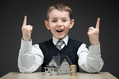 Weinig jongen met huismodel en stapel van muntstukken Royalty-vrije Stock Afbeelding