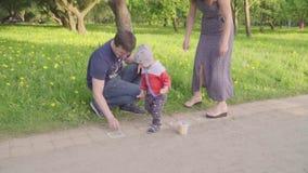 Weinig jongen met jonge ouders schildert krijt op asfalt Langzame Motie stock footage