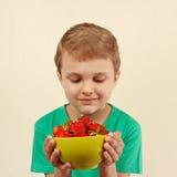 Weinig jongen met kom van verse rijpe aardbeien Stock Foto