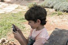 Weinig jongen met mobiel apparaat royalty-vrije stock afbeelding