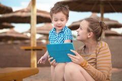 Weinig jongen met is moeder bij een strandtoevlucht royalty-vrije stock foto