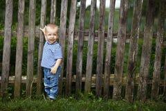 Weinig jongen met omheining in openlucht Stock Foto's