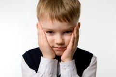 Weinig jongen met onverbiddelijk het denken op zijn gezicht royalty-vrije stock foto's