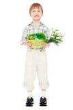 Weinig jongen met paaseieren en bloemen Stock Foto