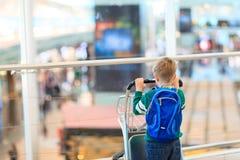 Weinig jongen met rugzak en karretje in de luchthaven Stock Afbeeldingen