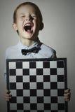 Weinig jongen met schaakbord Kinderenemotie Glimlach gelach Stock Fotografie