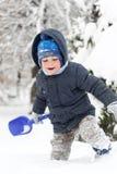 Weinig jongen met schop het spelen in sneeuw Stock Afbeelding