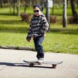 Weinig jongen met skateboard op de straat Stock Afbeelding
