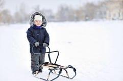 Weinig jongen met slee in de winter Stock Foto