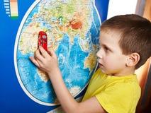 Weinig jongen met stuk speelgoed auto dichtbij wereldkaart Royalty-vrije Stock Afbeelding