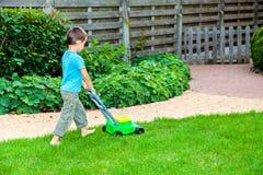 Weinig jongen met stuk speelgoed grasmaaimachine royalty-vrije stock afbeeldingen