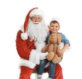 Weinig jongen met stuk speelgoed konijntjeszitting op authentieke Santa Claus Royalty-vrije Stock Foto
