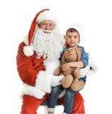 Weinig jongen met stuk speelgoed konijntjeszitting op authentieke Santa Claus Royalty-vrije Stock Fotografie