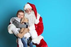 Weinig jongen met stuk speelgoed konijntjeszitting op de authentieke overlapping van Santa Claus ` stock foto