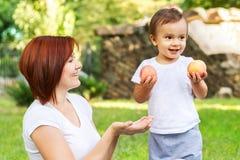 Weinig jongen met twee perziken en zijn mamma op de picknick in het park De zoon houdt vruchten terwijl de moeder vraagt om te de royalty-vrije stock afbeelding