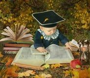 Weinig jongen met vele boeken in parkcollage stock foto's
