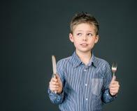 Weinig jongen met vork en mes. Hongerig kind. Stock Fotografie