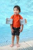 Weinig jongen met wapen drijft & zwemmend kostuum door de pool Stock Foto