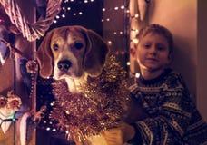 Weinig jongen met zijn hondzitting op het verfraaide venster voor Christmass-Vooravond Royalty-vrije Stock Fotografie