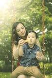 Weinig jongen met zijn moeder op de schommeling Royalty-vrije Stock Foto