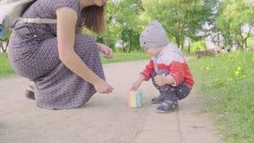 Weinig jongen met zijn mooie moeder schildert krijt op asfalt Langzame Motie stock videobeelden