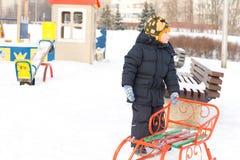 Weinig jongen met zijn slee in de wintersneeuw Stock Foto's