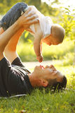 Weinig jongen met zijn vader op de aard Royalty-vrije Stock Afbeeldingen