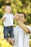 Weinig jongen met zijn vader op de aard Stock Afbeelding