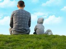 Weinig jongen met zijn vader op het groene gras Royalty-vrije Stock Foto's