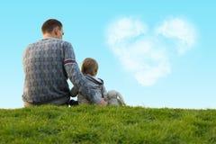Weinig jongen met zijn vader op het groene gras Stock Afbeeldingen
