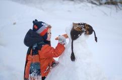 Weinig jongen neemt een wortel voor de neus van een sneeuwman op royalty-vrije stock afbeeldingen
