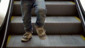 Weinig jongen neemt op de roltrap toe De jongen daalt op roltrapstappen in winkelcentrum Kerstmis die, idee voor uw ontwerp winke stock footage