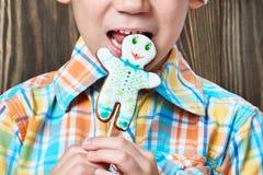 Weinig jongen in Nieuwe Year& x27; s rood GLB eet Kerstmiskoekjes Royalty-vrije Stock Fotografie