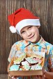 Weinig jongen in Nieuwe Year& x27; s rood GLB met doos van Kerstmiskoekjes Royalty-vrije Stock Foto