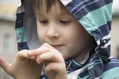 Weinig jongen nieuwsgierig van zijn hand stock afbeeldingen