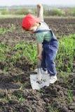 Weinig jongen om met grote schop te graven Stock Fotografie